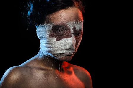 wounded bloody woman on black background with copy space