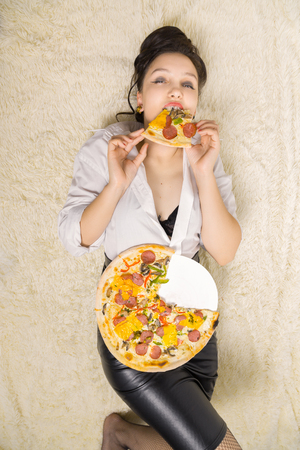beautiful overeat businesswoman lying with pizza pieces eating