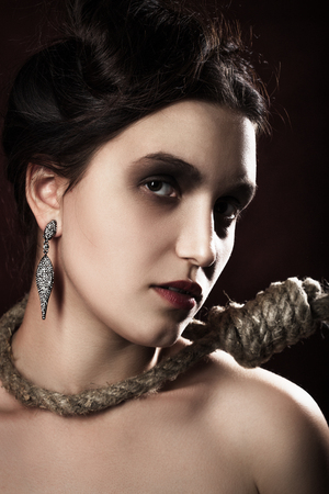 sad luxury woman with noose on dark red background looking at camera