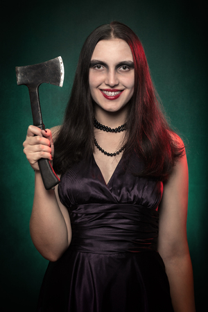luxury woman with axe on dark green background looking at camera