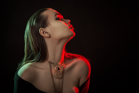 sensual luxury woman in jacket on black background show bare shoulders multicolor light Stock Photo