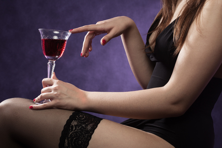 woman in stockings with red wine sitting at purple background