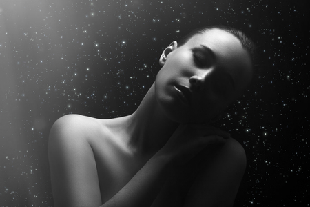 sad woman with closed eyes relax sitting on stars sky background under light rays, monochrome image