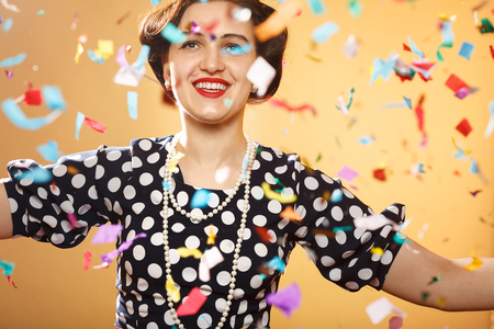 Happy girl on yellow background, colorful confetti slowly scatter and fall