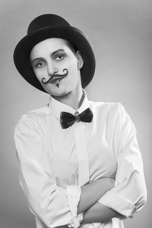 fun serious woman with hat, tie and moustache at gray background looking at camera, monochrome