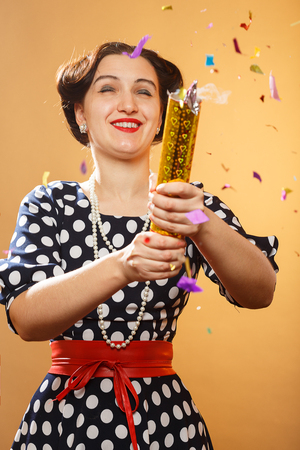 Happy girl on yellow background blows up cracker, colorful confetti slowly scatter and fall
