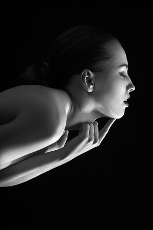sensual aroused woman with closed eyes head up on black background  Stock Photo