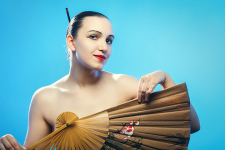 shirtless beautiful woman with japanese fan on blue background