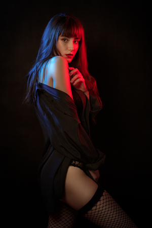 sensual serious woman in multicolor lights on black background looking at camera