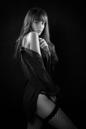 sensual woman on black background looking at camera monochrome