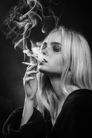 sad young blond woman on dark background smoking, monochrome 스톡 콘텐츠