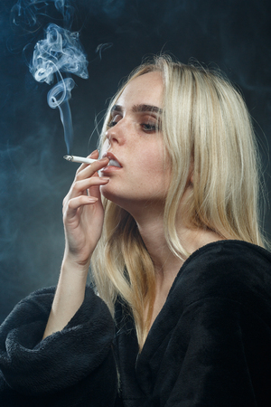 sad young blond woman on dark blue background smoking