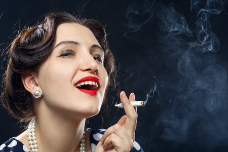 blond young woman smoking joint on black background Stock Photo