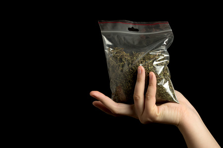 hand with pack of marijuana on black background Stock Photo