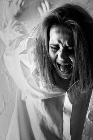 crazy woman with fluffy hair near wall screaming, monochrome