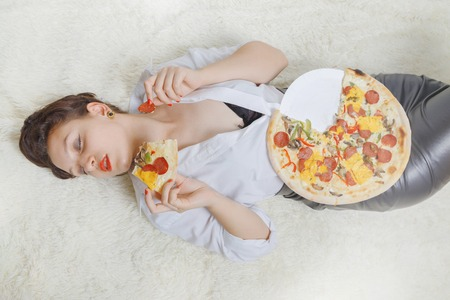 beautiful overeat businesswoman lying with pizza pieces Stock Photo