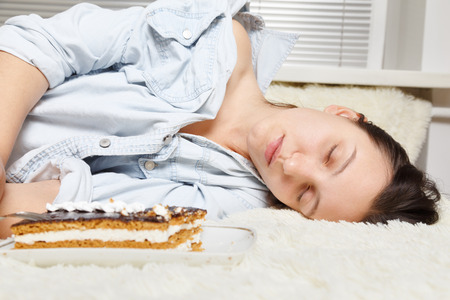 overeat young woman with sweet cake lying on bed Stock Photo