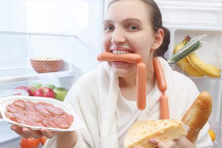 hungry fun woman with food near opened refrigerator smiling