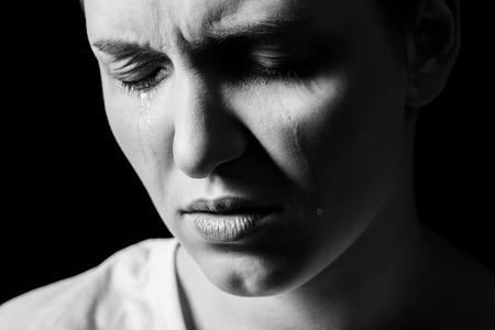 sad woman crying on black background, closeup portrait, monochrome