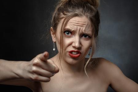 angry beautiful woman point at camera screaming Stock Photo