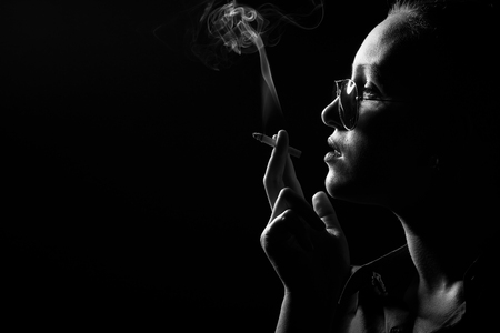 serious woman smoking cigarette on black background, profile view, monochrome Stock Photo