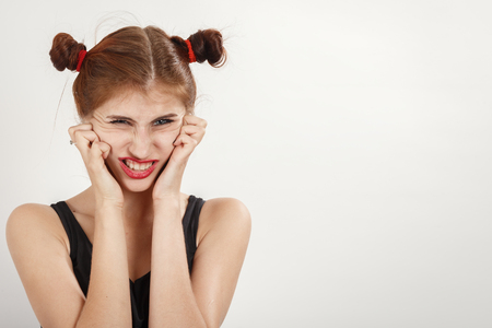shocked young woman on white background with copy space making grimace