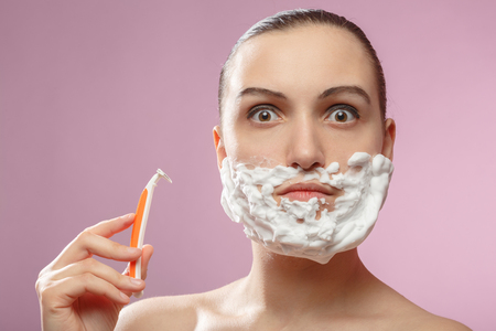 beautiful woman with fake mustache, beard and disposable razor on pink background has shave