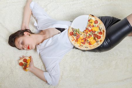overeat woman with pieces of pizza on white background