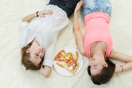 overeat happy girls lying on bed eats pizza, smiling