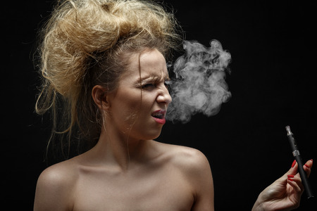 young woman smoking electronic cigarette on black background, grimacing, cough Stock Photo