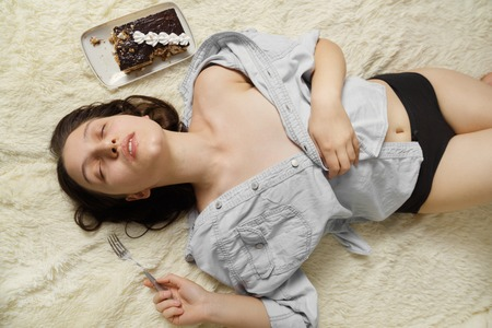 overeat young woman with sweet cake lying on bed, closed eyes Stock Photo