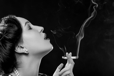 sensual young woman smoking joint on black background, monochrome