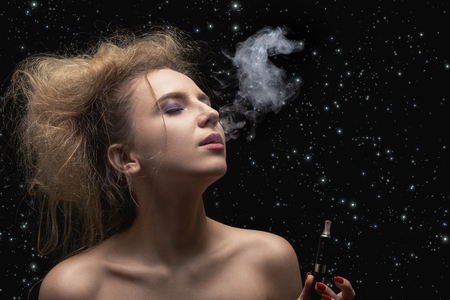 young woman smoking electronic cigarette on stars sky background