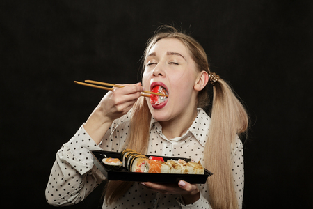 hungry young woman eats sushi on black background