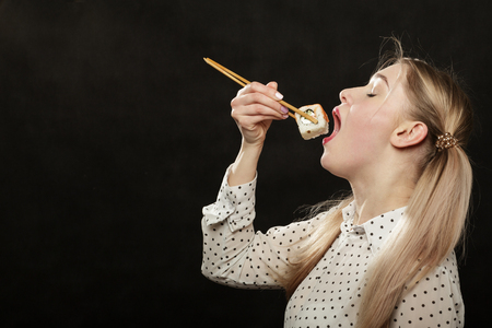 happy young woman eats sushi on black background with copy space Stock Photo