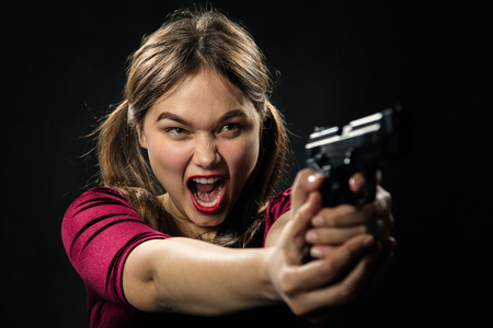 angry girl with gun on black background aiming, screaming Stock Photo