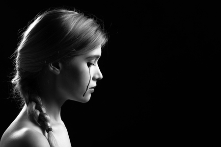 sad young woman crying on black background with copy space, side view, monochrome Foto de archivo