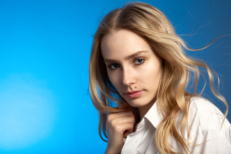 beautiful blonde young sensual woman in white blouse on blue background