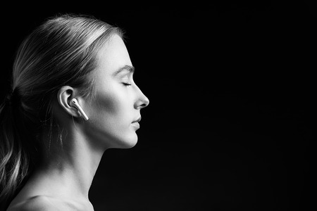 profile of blonde young woman with bluetooth earphones and closed eyes on black background, monochrome Stock Photo