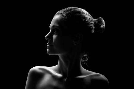 beautiful female profile with shoulders on black background, monochrome