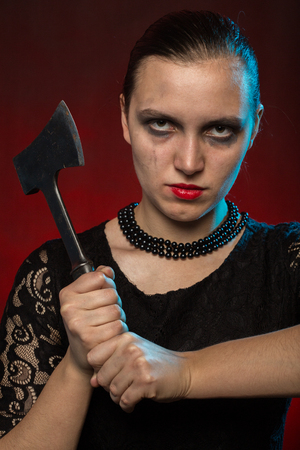 serious angry woman with axe looking at camera on red background