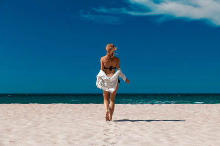 single young woman in swimsuit and white blouse at sand sea beach with blue sky
