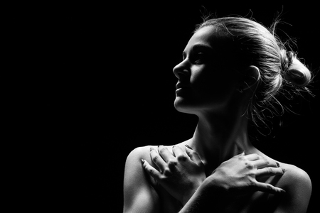 beautiful female profile with bare shoulders on black background with copy space, monochrome Stock Photo