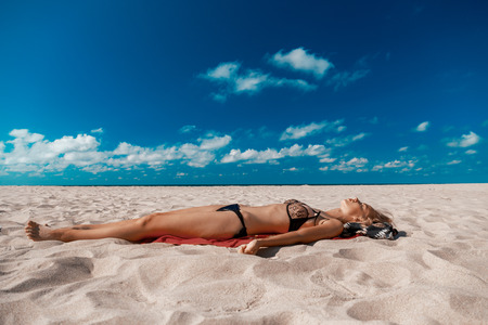 single topless young woman in swimsuit at sand sea beach with blue sky and clouds tanning lying Stock Photo
