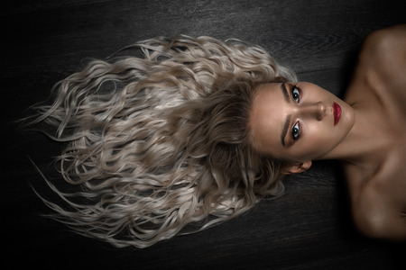 sensual curly blond woman lying on floor looking at camera Foto de archivo - 107418748