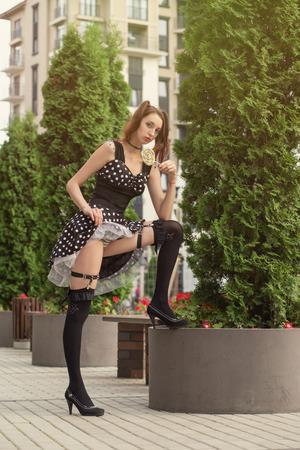 attraktive junge Frau mit Lutscher im schwarzen Kleid zeigen ihre schönen Füße in schwarzen Strümpfen auf der Straße