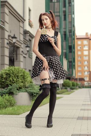 attractive young woman with lollipop in black dress show her beautiful feet in black stockings standing on street