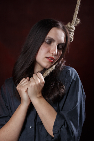 sad woman with noose on red background, closed eyes Standard-Bild - 108569897