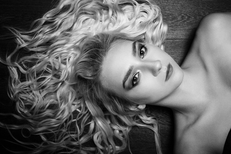 sensual curly blond woman lying on wooden floor looking at camera, monochrome Foto de archivo - 109807771