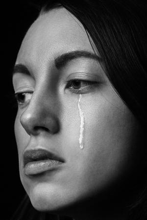 traurige Frau, die auf schwarzem Hintergrund weint, Nahaufnahmeporträt, monochrom